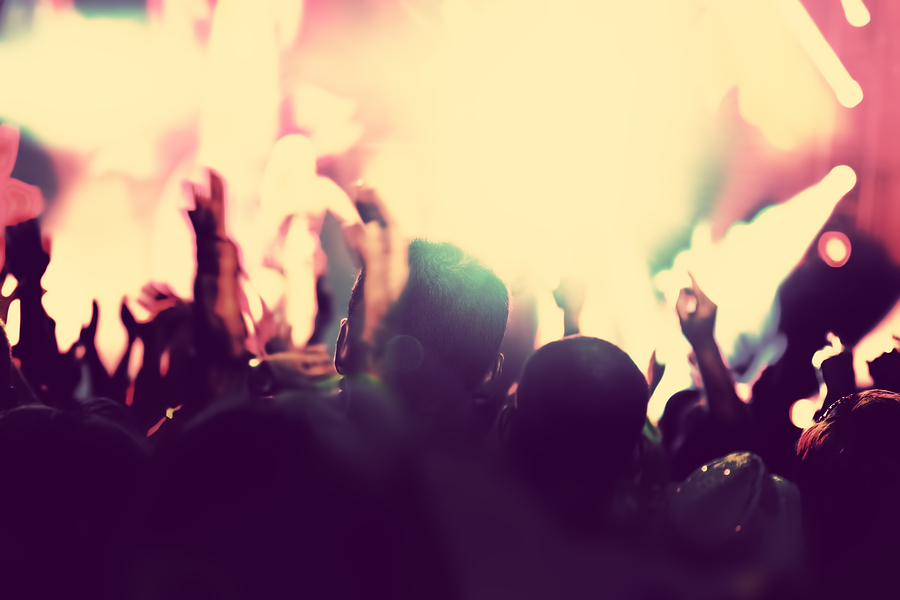 Concert, disco party. People with hands up having fun in night c