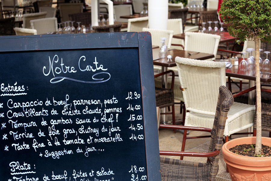 Typical cafe scene in Paris with menu board and tables and chairs arranged on the street.