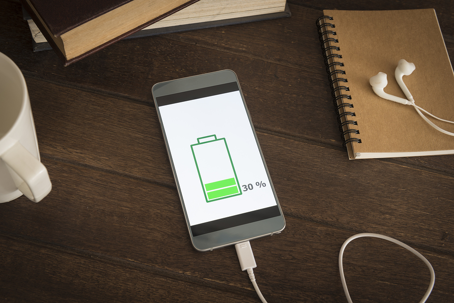 Mobile smart phones charging on wooden desk