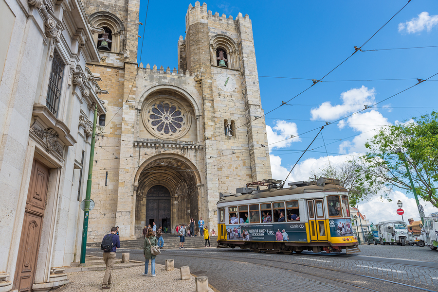 Historic Yellow Tram In Front Of The Lisbon Cathedral
